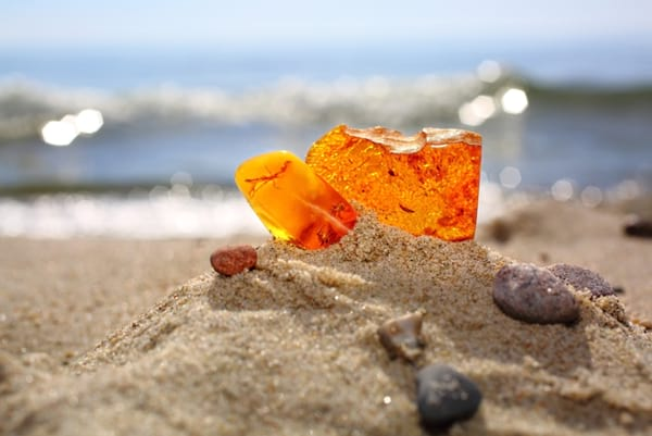 Two pieces of a transparent mineral of a sunstone against a background of a sea