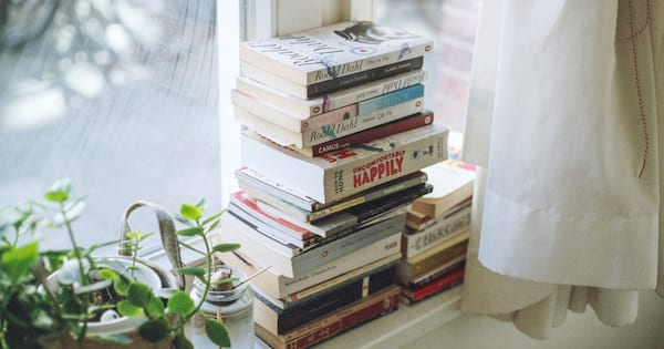 A large stack of books sitting on a windowsill