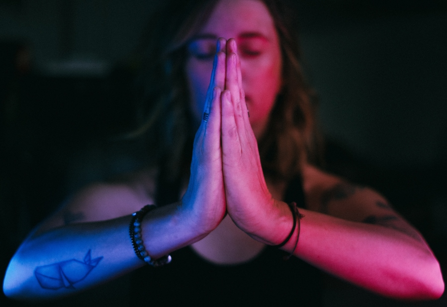 Woman with her hands together, meditating.