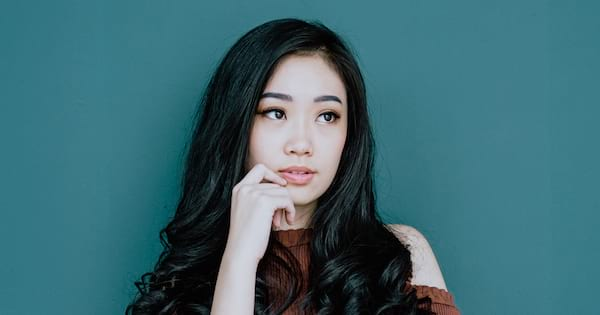 beauty, closeup of an asian woman with long wavy hair touching her chin, skincare instagram captions