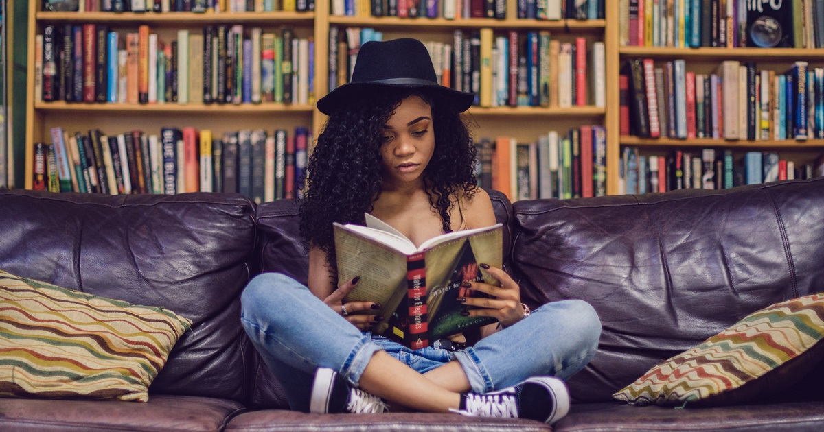 A teen black girl sits on a couch reading a book. She's wearing a hat and has curly long hair., school