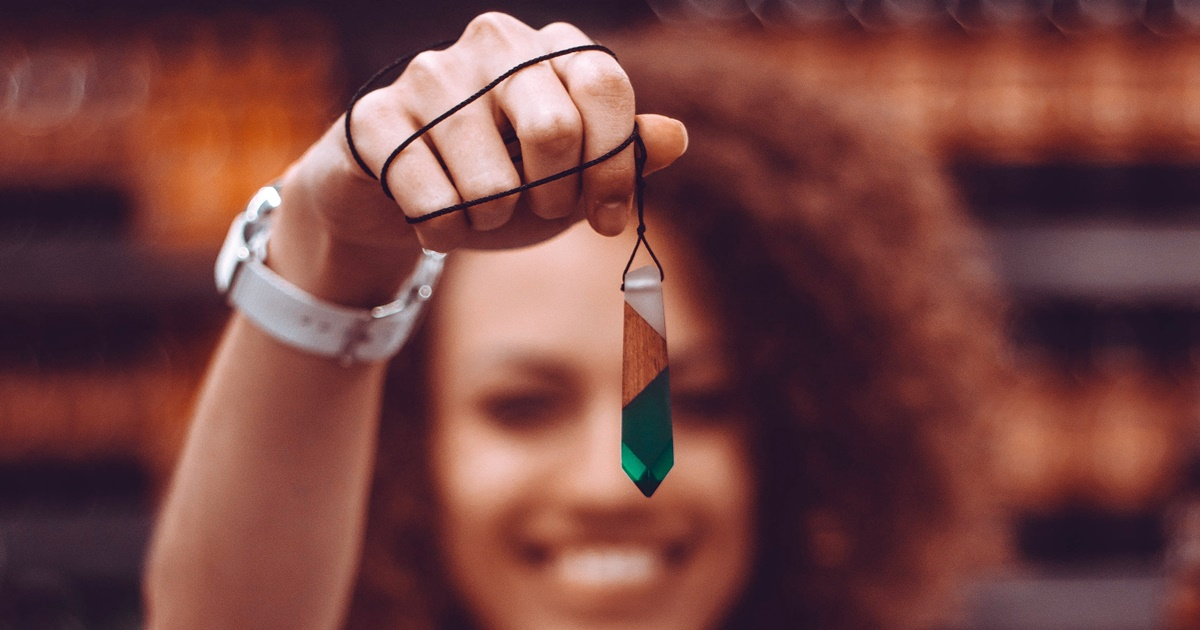 culture, closeup of a racially ambiguous smiling woman with curly brown hair holding up a crystal necklace, crystal instagram captions