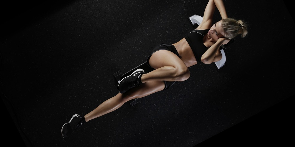 One woman doing exercise crunches and an abdominal workout on a dark background., fitness