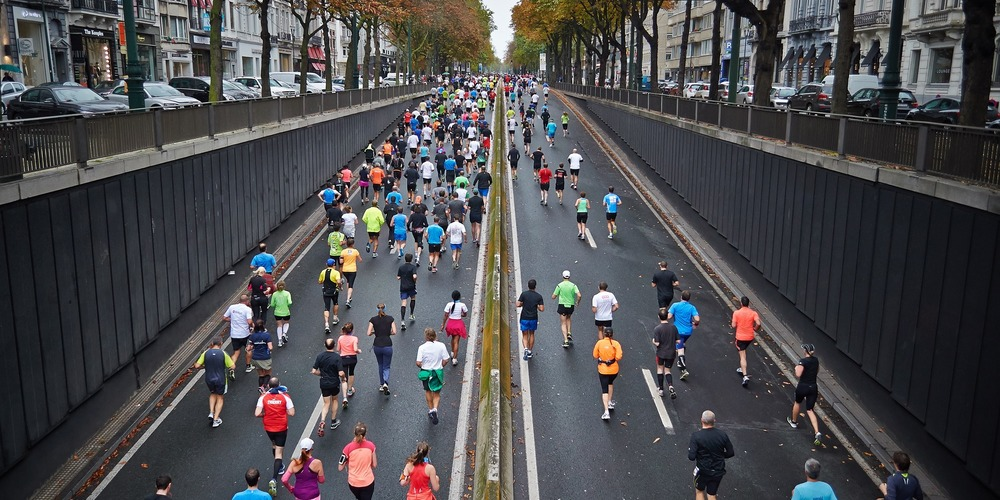 fitness, many runners running together in a group on the roadway during a marathon race, marathon instagram captions