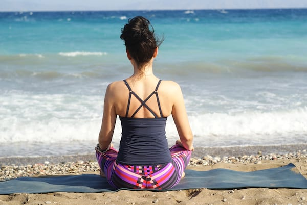 A cross-legged woman in a blue shirt and bright leggings sits on a yoga mat by the beach., fitness
