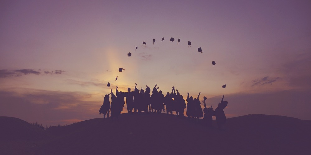 school, a group of college graduates silhouetted against the sun throwing their graduation caps into the air in an arc, college instagram captions