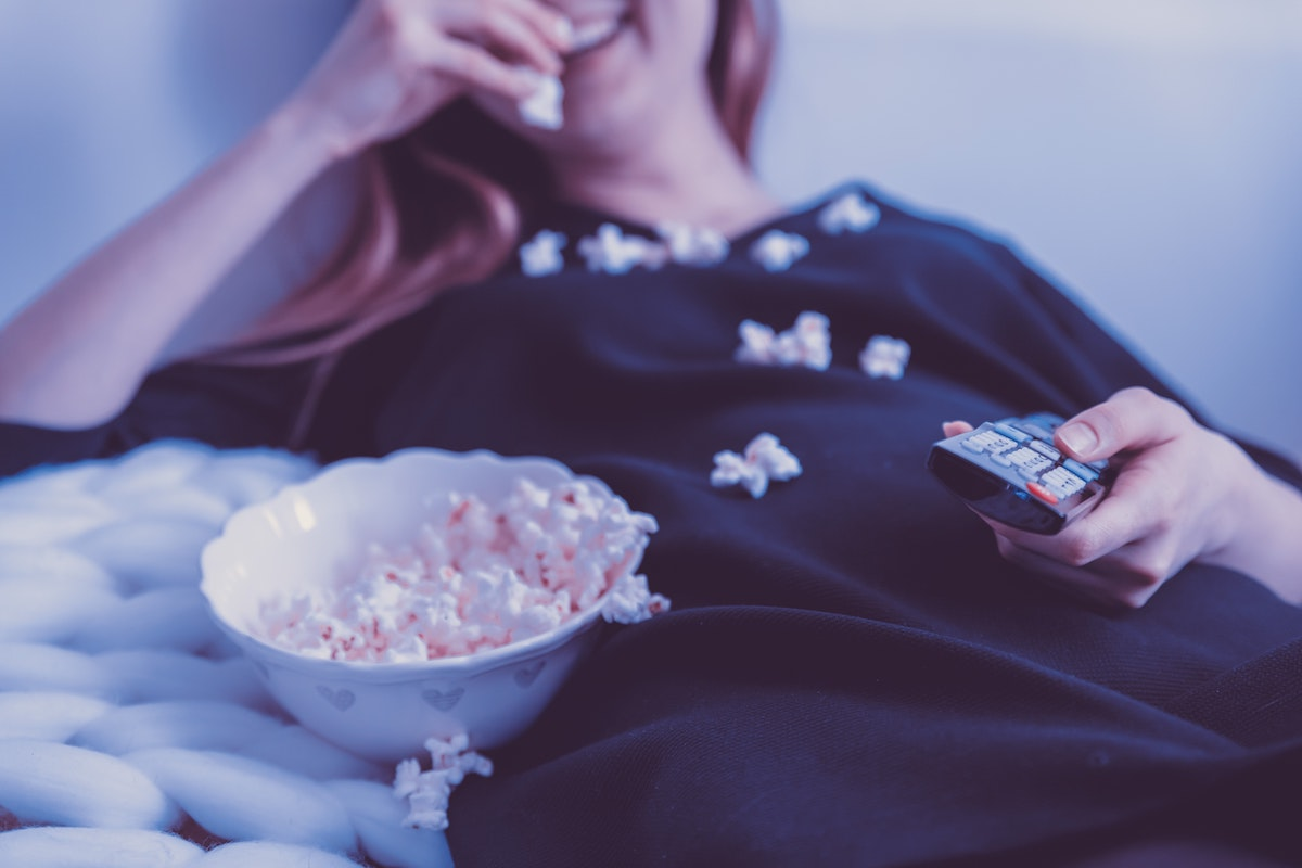 woman eating popcorn on the couch holding a TV remote
