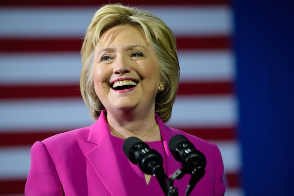 Hillary Clinton smiling in magenta suit speaks at a rally at the Charlotte Convention Center in a joint appearance with the US President