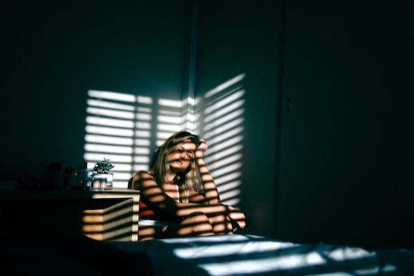 girl in the shadow of a window, on her bed