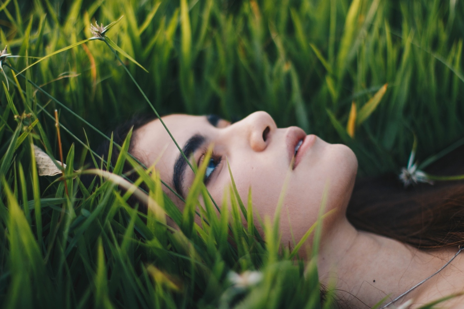 A woman laying down on grass looking up.
