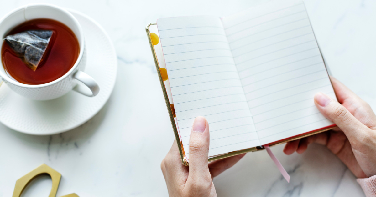 Person holding notes beside white ceramic teacup on white ceramic saucer