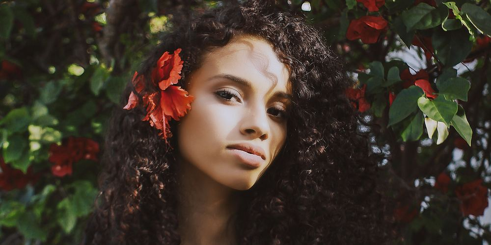 Woman with red flower in hair in front of tree, no makeup instagram captions, beauty