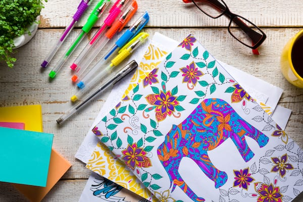 Retro desk with adult coloring books, stress relieving trend, mindfulness concept