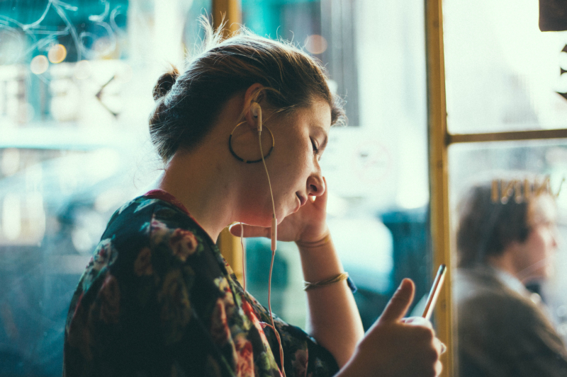 Woman listening to music on her iPhone using white earphones