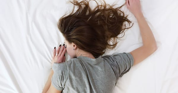 Girl wearing a grey T-shirt laying face down on her white bed