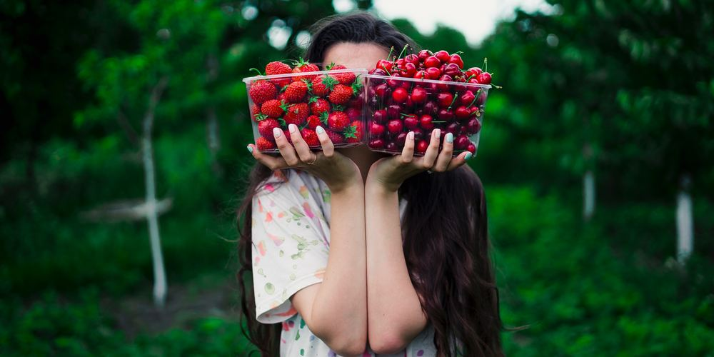 Woman holding up a box of strawberries and a box of cherries in a garden, paleo instagram captions, health