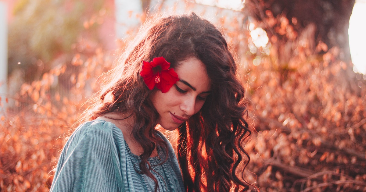 closeup of a white woman looking down, she has a red flower in her curly brown hair and is outside during twilight, facial instagram captions, beauty