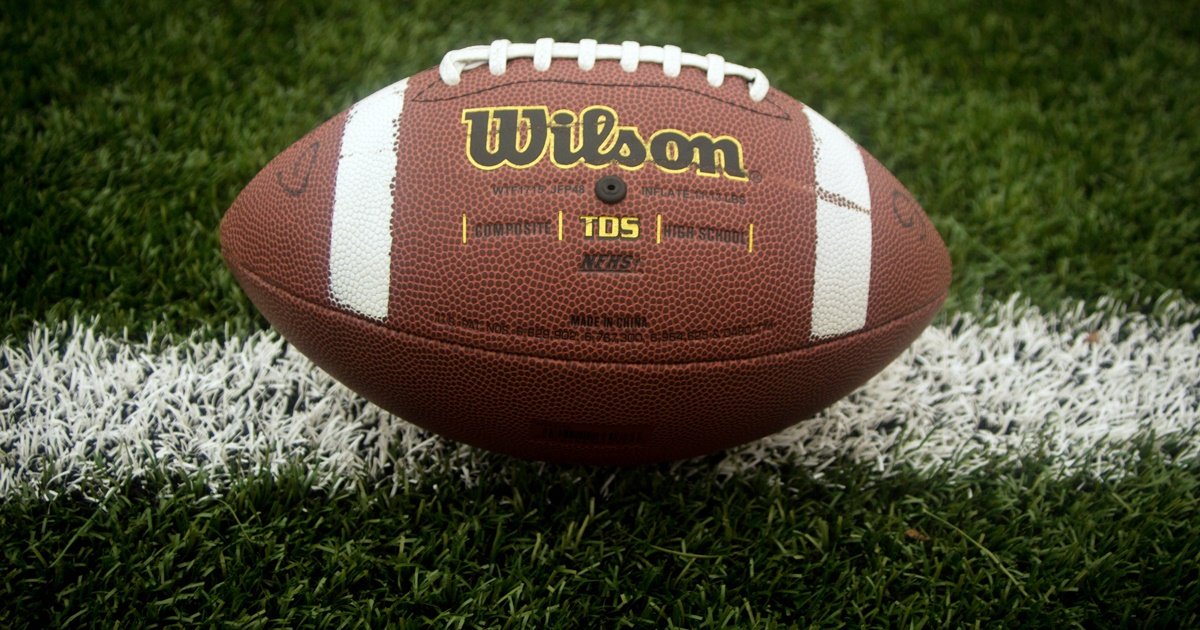 Closeup of a Wilson football resting on one of the painted white lines on a football field., culture