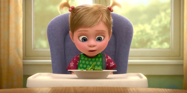 Baby Riley from Pixar's Inside Out sits in her high chair in front of a bowl of broccoli., movies