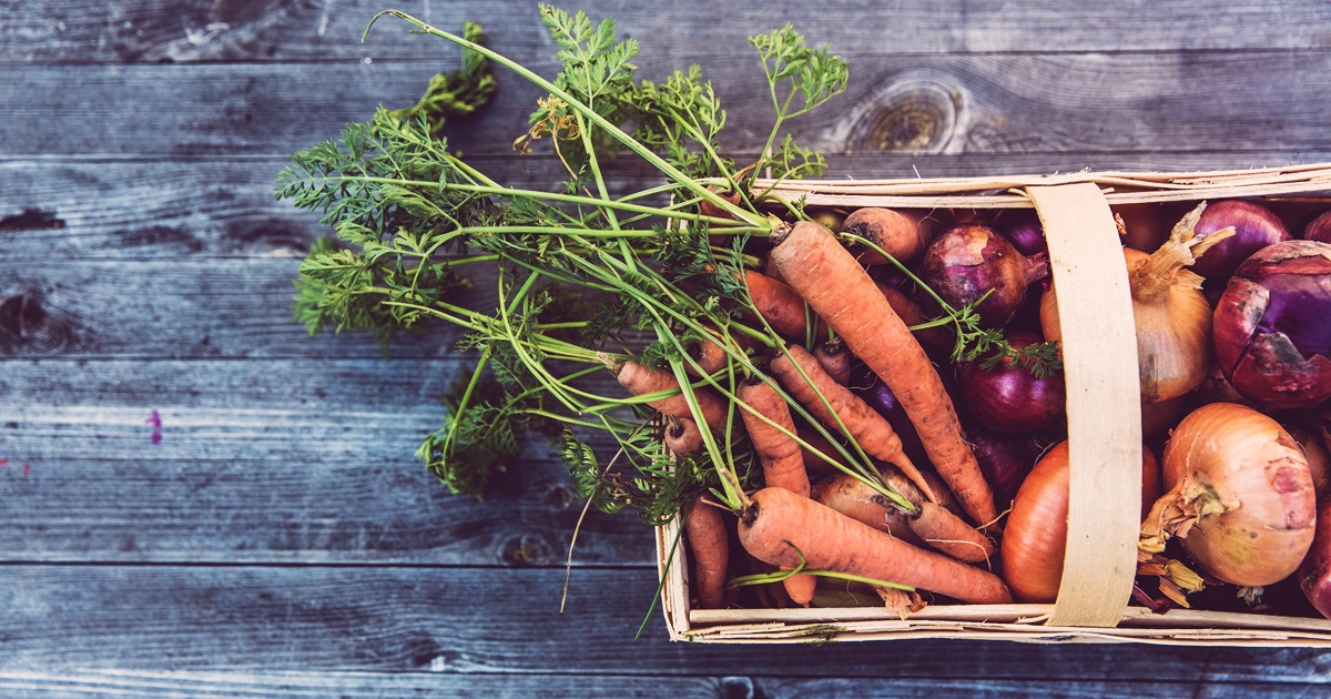 graying wood, a basket of fresh carrots and red and white onions from a farmer's market, farmer's market instagram captions, food & drinks