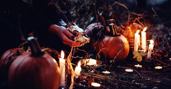 A wish sitting on the ground in the woods, pop culture, culture, their face not visible, they are holding an animal skull and surrounded by candles and pumpkins, witch costume instagram captions