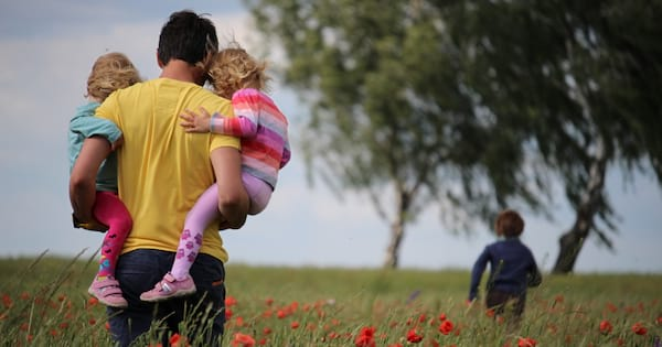 Man carrying his daughters in a field of red flowers