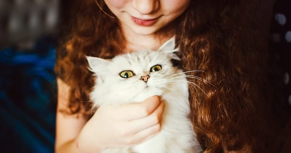 A woman cuddling a fluffy white cat with yellow eyes, animals, cat instagram captions