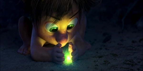 Cave boy from Pixar's The Good Dinosaur looks at a firefly through his hands., movies