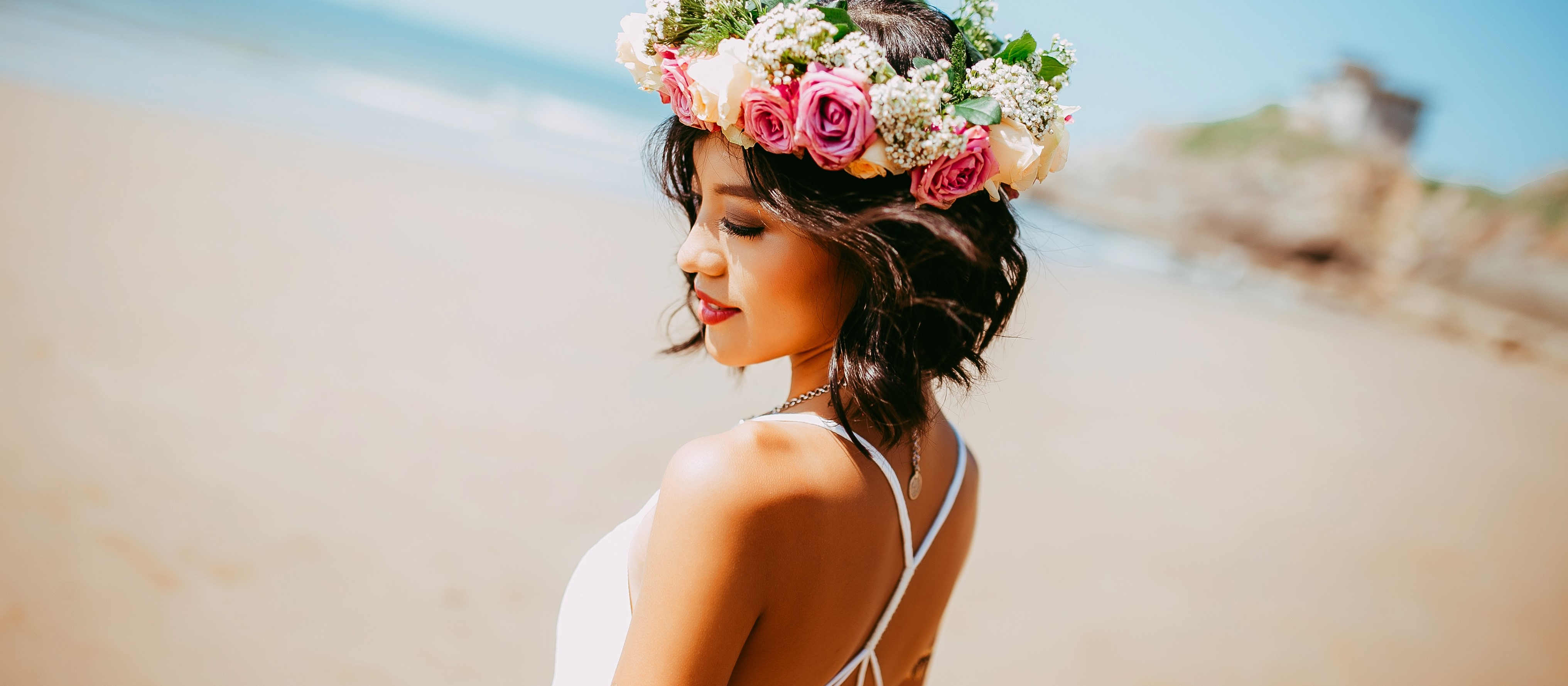 sea instagram captions, asian girl with flower crown in front of the ocean happy