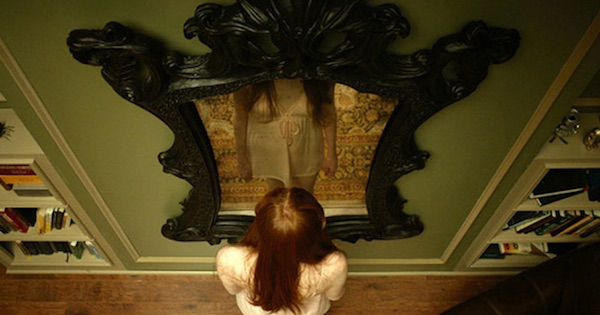 woman stands in front of Oculus mirror horror movie