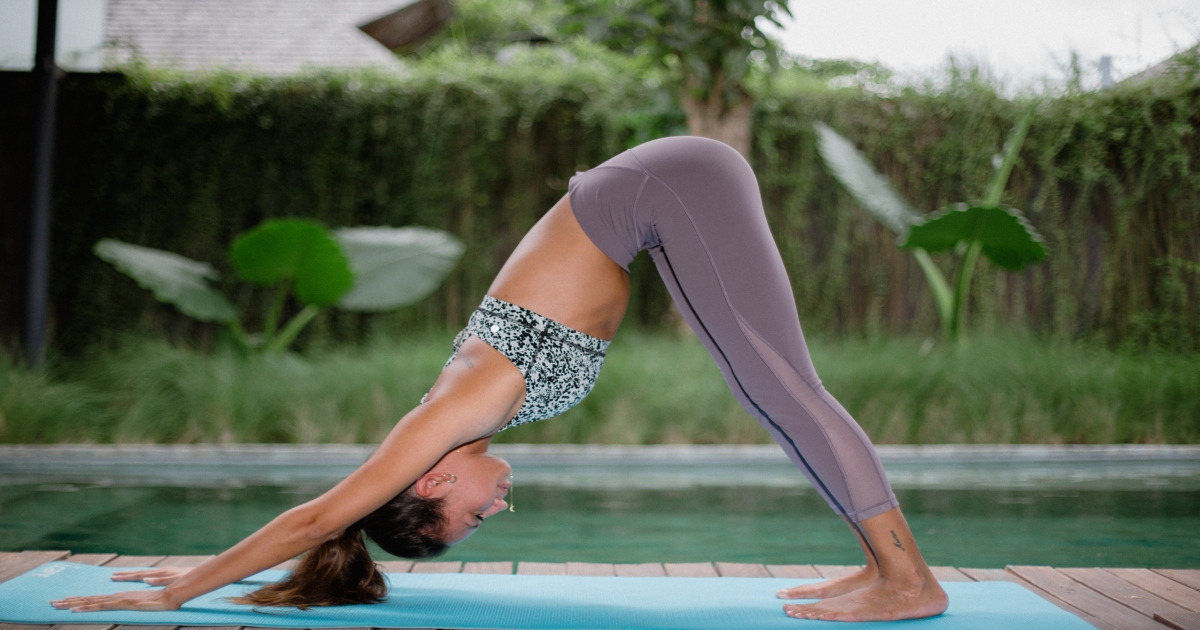 A woman practicing the downward dog yoga position.