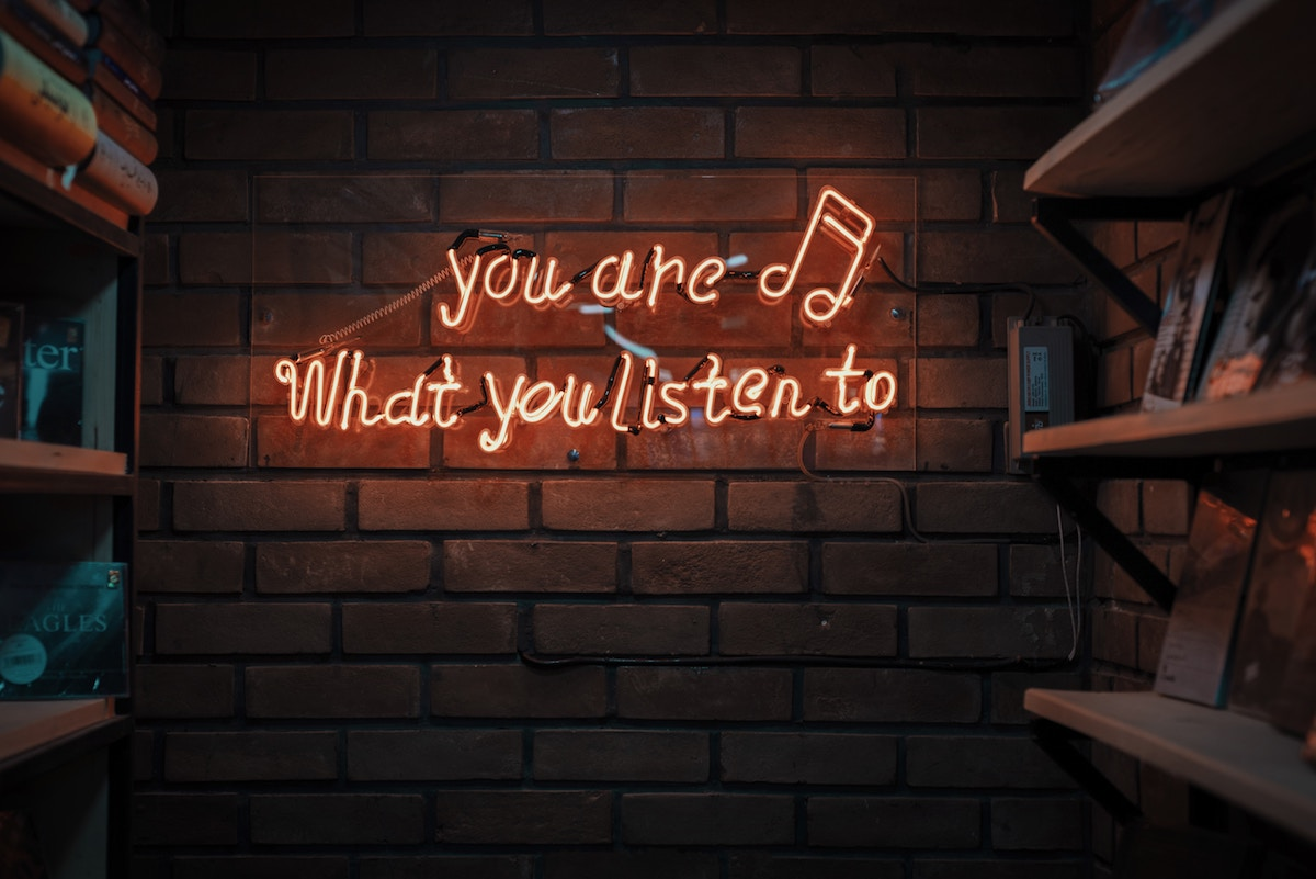 you are what you listen to, neon sign on brick wall that says