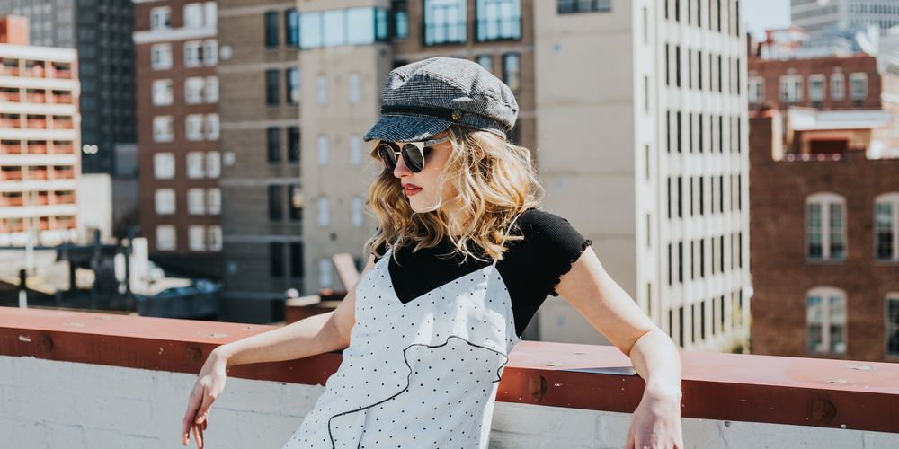 Woman in white dress and grey hat leaning arms on balcony edge, sassy instagram captions