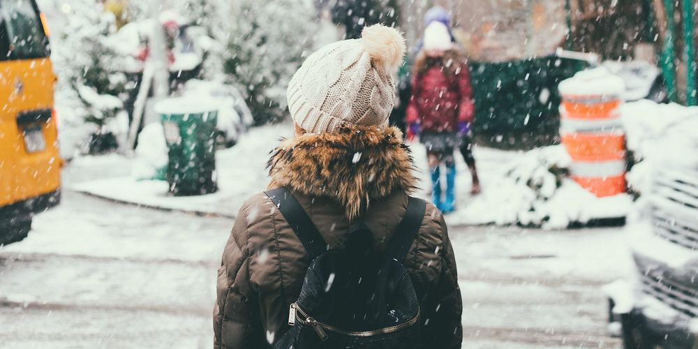 Woman in white hat and brown coat standing on city sidewalk while it is snowing, winter instagram captions