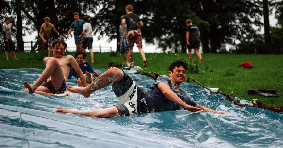Frat boy Instagram captions, several frat boys slide down a Slip 'n Slide while others stand around in the background, school