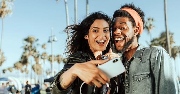 Selfie Sunday Instagram captions, a woman and man smile widely and take a selfie outside, culture
