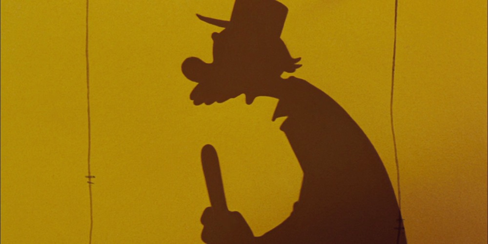 Joe from Disney's Dumbo stands silhouetted behind a tent speaking with a ring master