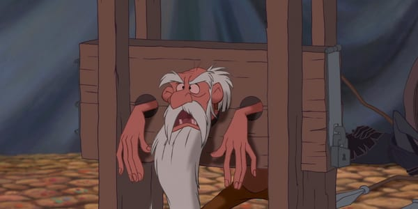 movies, the Old Prisoner from Disney's the Hunchback of Notre Dame stands trapped in a head and hands vice