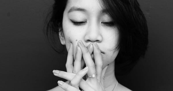 Black and white close up photo of a woman, with her hands on her face.