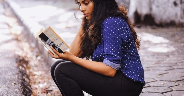 Deep Instagram captions, racially ambiguous woman with brown skin and brown curly hair sitting on a curb reading a book