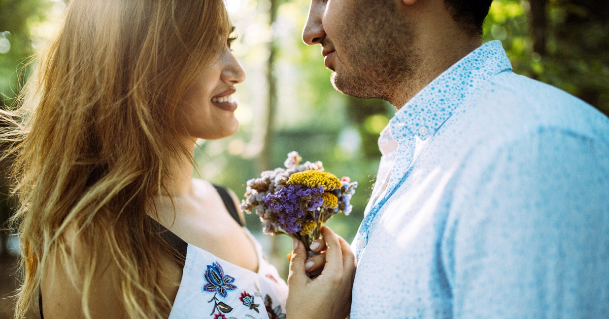 National Boyfriend Day Instagram Captions, a racially ambiguous straight couple stands close together, while the woman holds a small bouquet of flowers between them, relationships