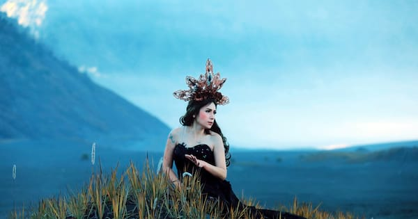 Mermaid costume Instagram captions, photo of a white woman wearing a black gown perched in the sea grass wearing a crown