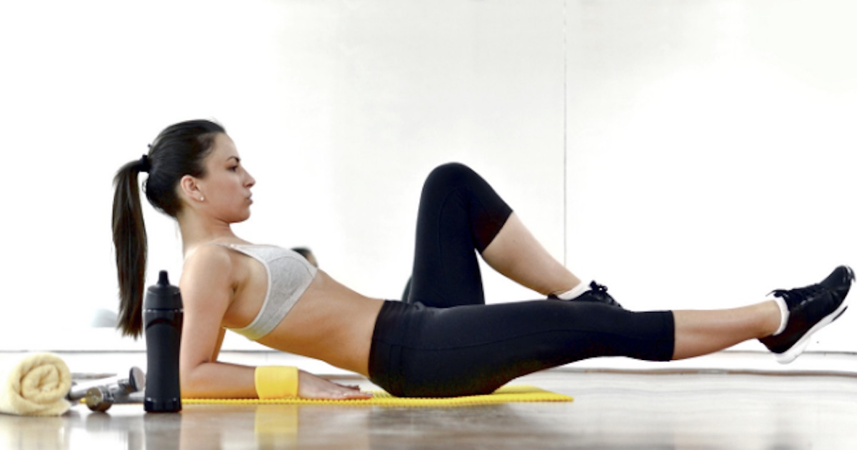 woman laying on yoga mat facing up with one leg in air