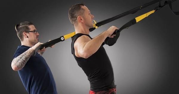 two men performing TRX exercises, health fitness