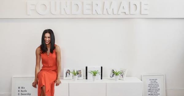 FounderMade's Meghan Asha sitting in front of a white wall that reads \FounderMade\