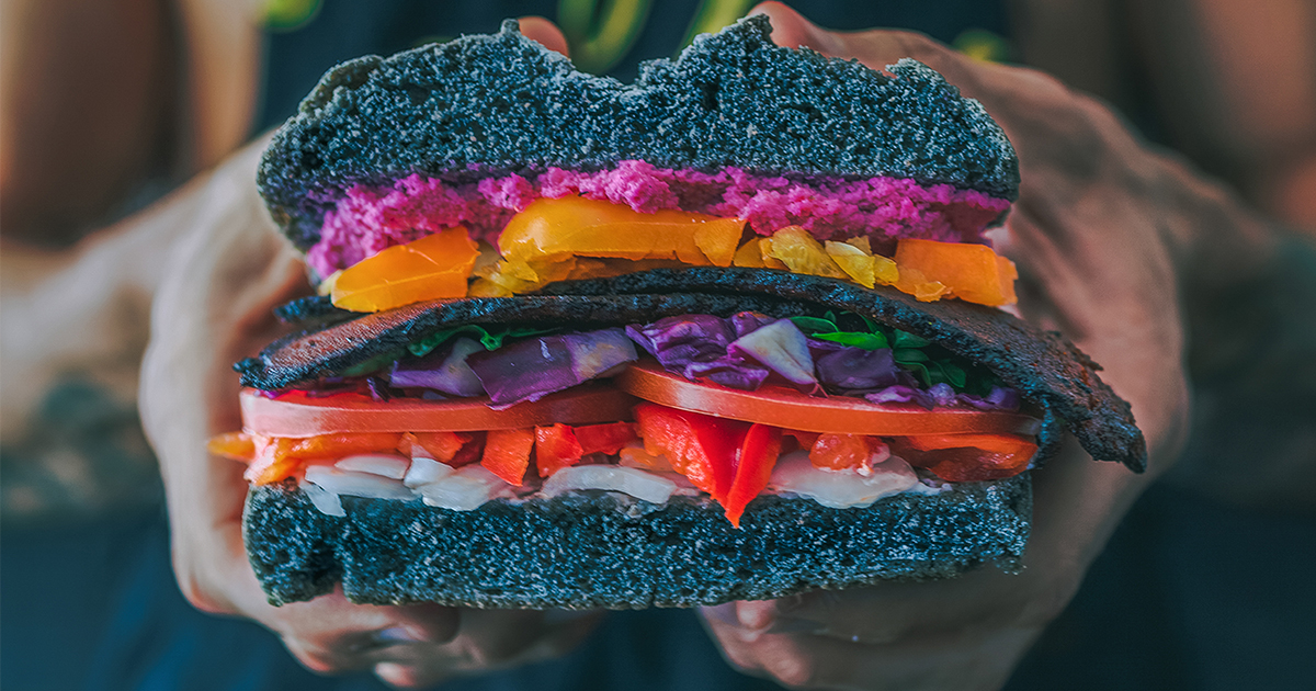Vegan fast food for 2018, woman holding a colorful veggie burger