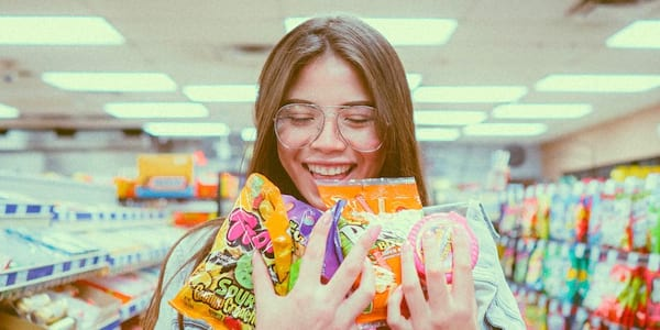 Woman smiling and holding candy bags in a store, culture, pop culture, halloween weekend instagram captions