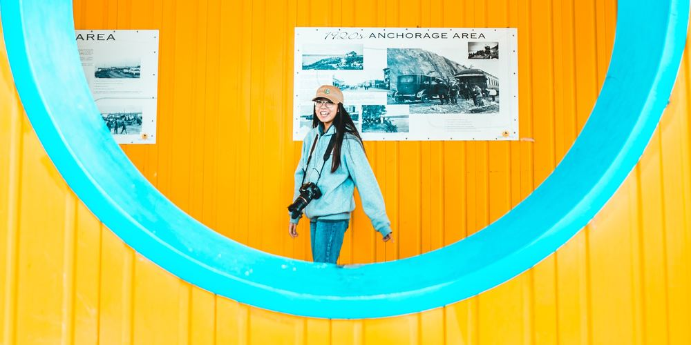 creative instagram captions, Smiling woman standing in a yellow room framed by a blue window