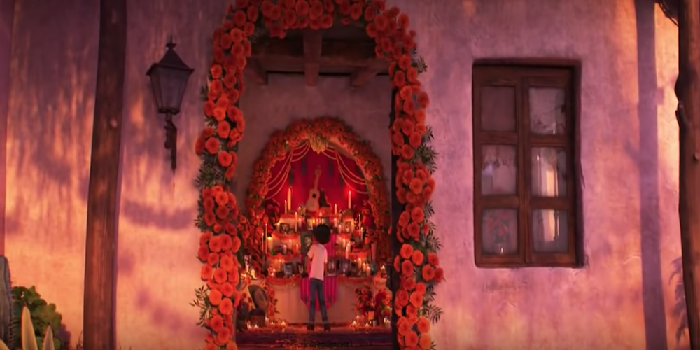 The orange-flowered ofrenda room of the Rivera family with Miguel standing in it from Pixar's Coco., movies