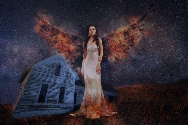 woman with wings in front of abandoned house, haunted house instagram captions